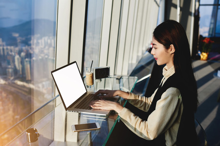 Asian woman professional journalist is working on her new article on laptop computer, while is sitting in co-working space near window with view of metropolitan city in China during business trip