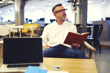 Mindful male executive thinking over plot of detective story reading favorite book while resting during break while waiting for email message using laptop computer Stock Photo