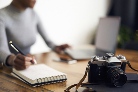 Picture of vintage camera on frontage standing near stuff of creative female journalist using it to make illustrative photo to articles while Stock Photo
