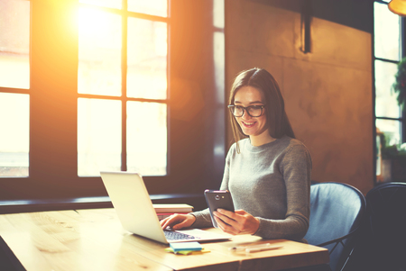 Experienced female editor in trendy eyewear of online issue coordinating work of content managers using laptop and wifi while