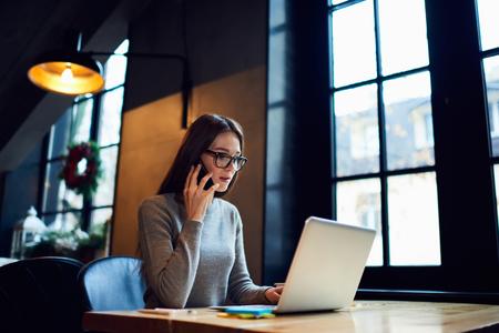 Jonge bekwame eigenaar van webwinkel blij om te horen over het verhogen van inkomsten uit verkoop en service praten op telefoon met administratief manager terwijl