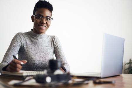 Het glimlachen van portret van bekwaam jong afro Amerikaans vrouwelijk ontwikkelaar controlerend werk van de marketing van deskundigen die rol van adverterende inhoud in Webhandel analyseren
