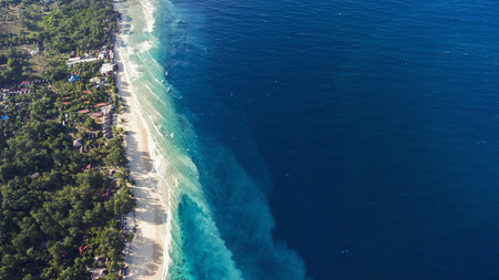 Top view aerial drone photo of stunning colored sea beach with crystalline water fringed with swaying tropical palms and leafy trees. Incredibly beautiful blue ocean meet with powder-white seashore Stock Photo