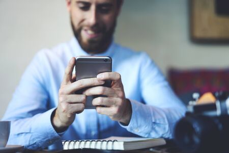 selected: online games using modern smartphone connected to 5G wireless internet completing levels during work break spending leisure time in coworking space Stock Photo