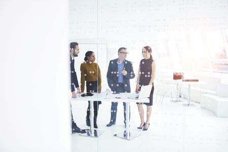Een team van bekwame webontwerpers die werken aan nieuw projectoverleg met een leider die op creatieve ideeën wacht, motiveerde medewerkers tot samenwerking