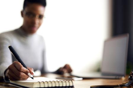 Getalenteerde vrouwelijke schrijver werkt aan de creatie van een nieuwe roman en noteert ideeën in een persoonlijk dagboek om de beste plotstrategie te kiezen om lezers te trekken die zich concentreren op werk in een persoonlijk kabinet, selectieve focus op pen