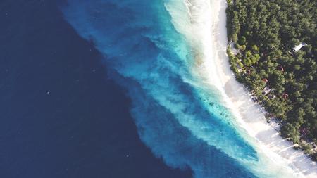 Luchtfoto drone foto van het bovenaanzicht van prachtige gekleurde zee strand met kristalhelder water. ongelooflijk mooie blauwe oceaan ontmoet met poeder-witte kust omringd door tropisch regenwoud of palm bomen jungle