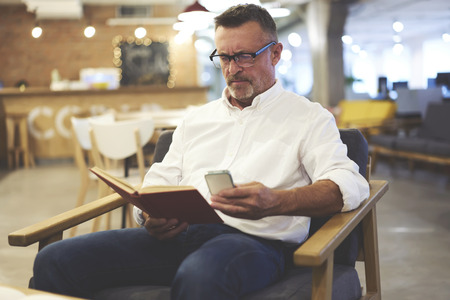 Handsome male dressed in trendy clothes fond of reading enjoying leisure spending with book taking photos of favorite paragraph to share