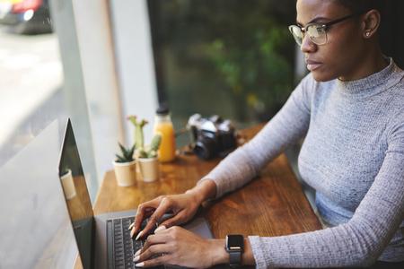 集中在眼镜的年轻女性文案键入在膝上型计算机键盘的键盘在社会的广告消息文本的键盘