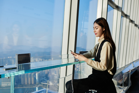 Woman successful lawyer is reading news in internet via cell telephone, while is waiting her client in modern interior with metropolitan city outside window. Young Japanese female is chatting on phone