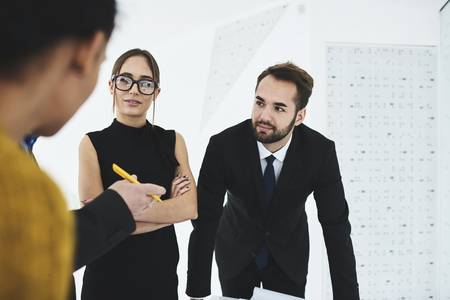 Portrait of male and female young talented journalist dressed in formal wear having interview with foreign investor listening attentively to speech about Stock Photo