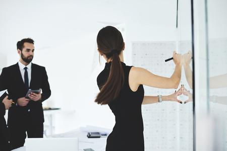 研修ワーク ショップより良いボード上のインフォ グラフィックを描画中に仕事の新しい概念を説明する熟練した女性ビジネス コーチの背面図