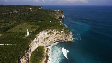 바위가 강력한 파도와 만나는 바다의 아름다운 해안의 조감도에서 봅니다. 절벽의 가장자리에 등 대 발리 해안으로 아름 다운 해변의 공중 무인 항공 스톡 콘텐츠