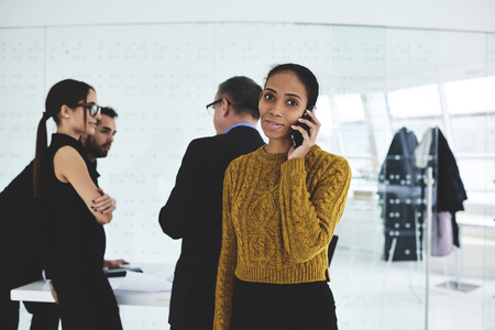 productive: Portrait of young afro american female administrative manager on frontage coordinated work of employees via phone talk while being on f