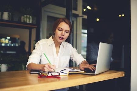 Geconcentreerde vrouwelijke administratief manager met behulp van database-informatie van cv van collega's maken financieel verslag van salarissen werken met behulp van laptop en draadloze verbinding met internet