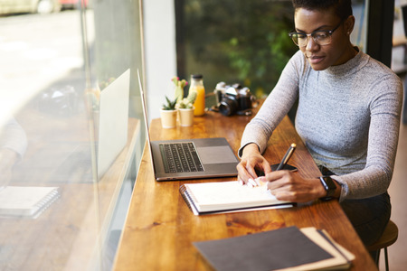 Skilled afro american female financier working overtime to finish report before leader council begins concentrated on accountings during break