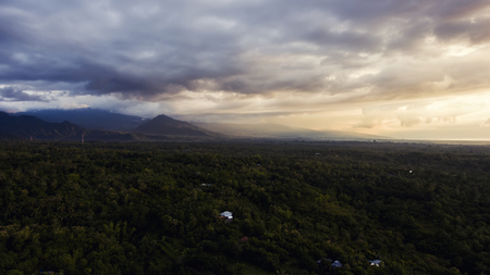 Aerial photo from airplane cockpit of a beautiful outdoors scenery with dramatic, white clouds with sunset rays over silhouette of mountains. Perfect background for website. Wonderful nature landscape 版權商用圖片