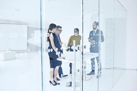 Leiders van handelsonderneming die samenwerken aan het ontwikkelen van nieuwe zakelijke projecten om creatieve oplossingen te vinden tijdens formele besprekingen met behulp van digitale apparaten Stockfoto
