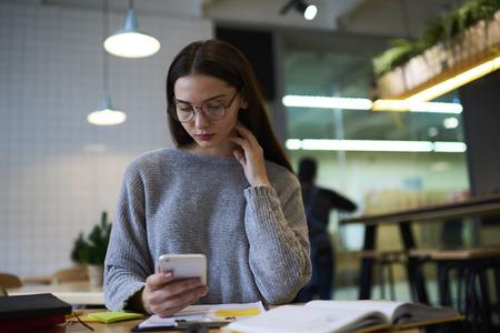 koncentrovaný: Mladý atraktivní ženské novinář odpočívá během práce v kavárně interiér sledování nejnovější loutkové hledání tématu