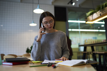 concentrate: Attractive professional female owner of cozy cafe working with documentation and financial reports while having phone