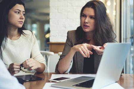 Geconcentreerde vrouwelijke correspondenten die informele bijeenkomst hebben tijdens de pauze in de koffiewinkel, die de taak bespreken voor de dag van de redacteur Stockfoto
