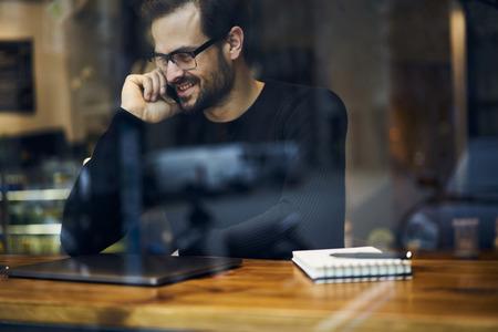 Vrolijke mannelijke reiziger blogger die telefoongesprek heeft dat vrije draadloze Internet-verbinding gebruikt die over avonturen spreekt Stockfoto