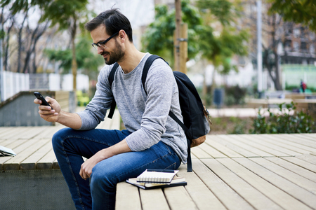 checking account: Skilled male international student resting during break in university using free wireless connection to internet in university wifi zone Stock Photo