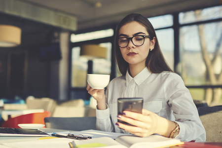 Confident female businesswoman reading latest news and searching marketing manager to provide advertising campaign