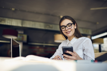 Cheerful young international student with charming smile chatting with best friends via smartphone connected to wireless internet in university Stock Photo
