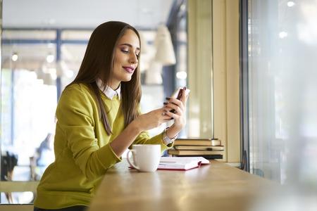 Encantador estudiante internacional de sexo femenino descansando después de las lecciones en la universidad sentado en la cafetería de comunicación a través de chat de vídeo Foto de archivo