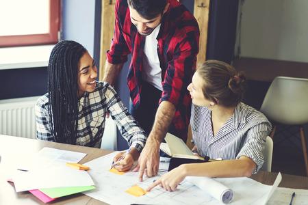 Jonge vrouwelijke studenten van architectenfaculteit van universiteit die in paren werken die blauwdruk voor de bouwbouw creëren die advies hebben