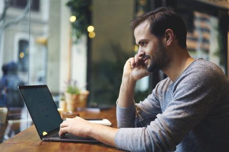 Knap mannelijk ondernemer het typen bericht aan tevreden manager van website van marketing bedrijf op toetsenbord van laptop computer