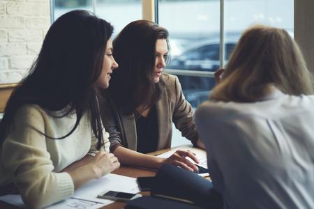 IT 企業を作るワーク ショップをコーディングのためのアプリケーションを使用する方法を説明する才能のある若い研修生の熟練した女性コーチ 写真素材