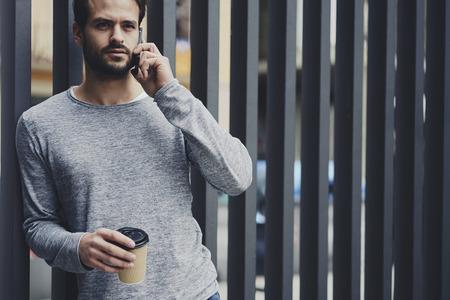 自信を持って男性起業家のものの仕事を制御する管理のマネージャーとのローミングに電話での会話を持っていること