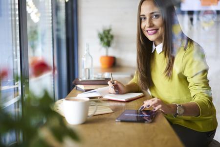 魅力的な女性のプロのジャーナリストのニュースを監視、プレスを作成しながら一杯のコーヒーとカフェで彼女の営業日を開始