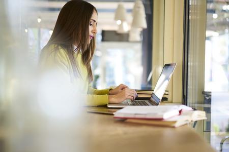熟練の成功した女性のコーヒー ショップでインターネット、ラップトップ コンピューターに無料のワイヤレス接続を使用しての作業