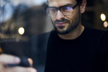 Getalenteerde knappe mannelijke internationale student chatten met vrienden in sociale netwerken delen van foto- en videobestanden Stockfoto