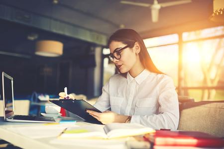 成功した戦略を開発収入を増やすものの職務のチェックリストを作るレストランの熟練した経験豊富な女性経営者