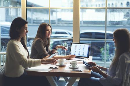 レストラン議論で非公式の会合を持つ商社の若い魅力的な熟練した女性起業家の所有者
