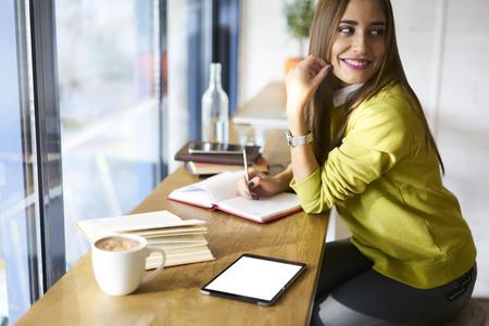 職員の組織化の詳細および準備の確認の作業を制御するコーヒー ショップの魅力的な女性管理マネージャー