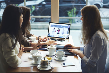 media gadget: Attractive hipster girls planning trip on weekends enjoying free time drinking tea in cafe using laptop computer with mock up screen