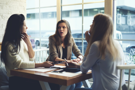 Group of young attractive well dressed women meeting after work in cafe to rest and have conversation sharing plans, showed and surprised woman listening story of her best friend female colleague Reklamní fotografie