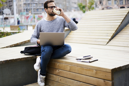 checking account: Young male skilled freelancer  working without breaks drinking coffee outdoors trying to fulfill task of client in time Stock Photo