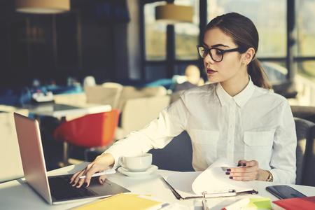 マニュアルやレストラン収入オンライン データベースの操作のレポートを確認エレガントな衣装で魅力的な女性エコノミスト