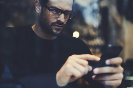 写真やビデオのファイルを共有する社会的なネットワークで友達とおしゃべり才能のあるハンサムな男性留学生