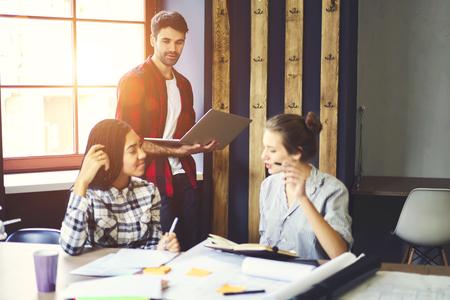 숙련 된 여성 연수생의 아이디어를 토론하고 랩톱 컴퓨터를 사용하여 마감 전에 프로젝트를 수행하기 위해 협력하는 회사에서 연습하는 제안을 듣는
