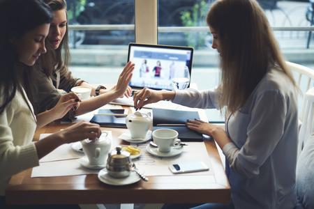 今後のお祝いのオンライン ショッピングのための服を選択する仕事の後休憩のカフェでお茶の時間を楽しんでいる美しい女性の親友 写真素材