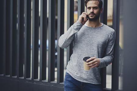 自信を持って男性起業家のものであることの仕事を制御する管理のマネージャーとのローミングに電話での会話を持っていること 写真素材