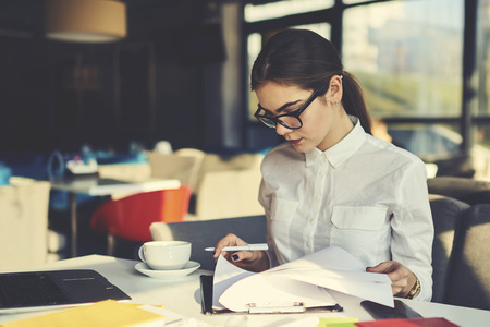 Skilled professional female administrative manager of coffee shop checking documentation for month before sending report to financier supervising working process and controlling stuff during revision Banque d'images