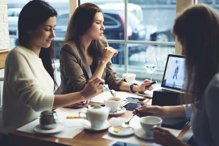 Web ストアの広告キャンペーンを作成するカフェでのコーヒー ブレーク中に働いている熟練した女性マーケティング専門家のグループ 写真素材